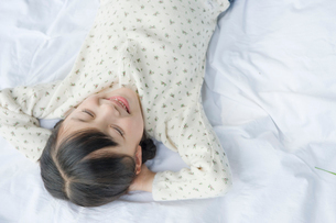 寝転がり目をつむる笑顔の女の子の写真素材 [FYI03362318]