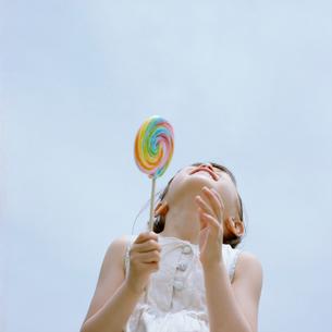 キャンディーを持ち笑う女の子の写真素材 [FYI03362320]