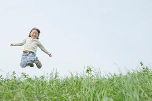 外でジャンプする女の子の写真素材 [FYI03362321]
