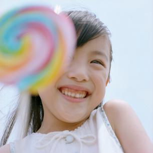キャンディーを持ち笑う女の子の写真素材 [FYI03362323]