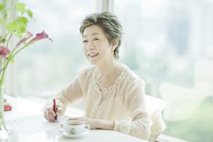 楽譜を書く笑顔の中高年女性の写真素材 [FYI03362465]
