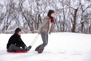 雪の中ソリで遊ぶ若い男女の写真素材 [FYI03362681]