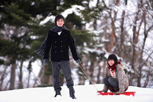 雪の中ソリで遊ぶ若い男女の写真素材 [FYI03362684]