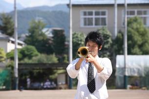 校庭でトランペットを吹く男子学生の写真素材 [FYI03362688]