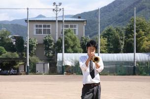 校庭でトランペットを吹く男子学生の写真素材 [FYI03362689]