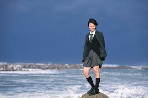 海のテトラポットに立つ女子学生の写真素材 [FYI03362695]