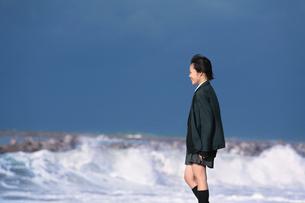 海のテトラポットに立つ女子学生の写真素材 [FYI03362696]