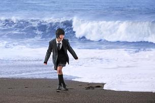 海の波から逃げる女子学生の写真素材 [FYI03362697]