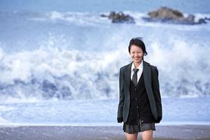 海の砂浜に立つ女子学生の写真素材 [FYI03362699]