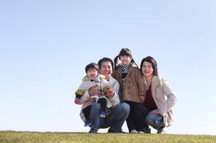 芝生の上で笑う家族の写真素材 [FYI03362702]