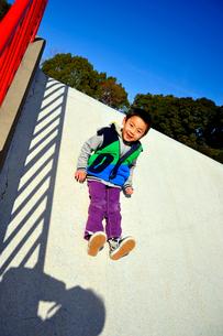 滑り台をすべる少年の写真素材 [FYI03362752]