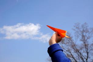 紙飛行機(オレンジ色)と少年の手の写真素材 [FYI03362803]