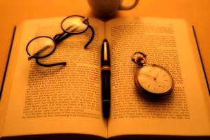 洋書の上の懐中時計と万年筆と眼鏡の写真素材 [FYI03362925]