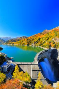 秋の立山・快晴の黒部ダムに遊覧船と観光放水に紅葉の写真素材 [FYI03364921]