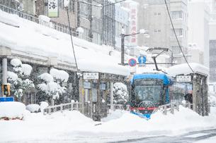 雪の中を走る万葉線ドラえもんトラム2の写真素材 [FYI03365043]