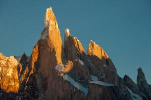 パタゴニアの針峰セロトーレの山頂部が日の出に染まるの写真素材 [FYI03365068]