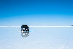 鏡張りのウユニ塩湖と車の写真素材 [FYI03365154]