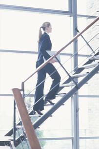 パソコンを持って階段を上るスーツ姿の女性の写真素材 [FYI03365484]