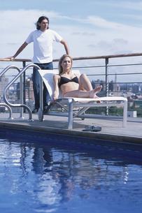 屋上のプールサイドの外国人カップルの写真素材 [FYI03365540]