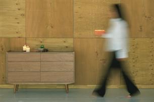 木の壁の部屋を歩く女性のシルエットの写真素材 [FYI03365554]