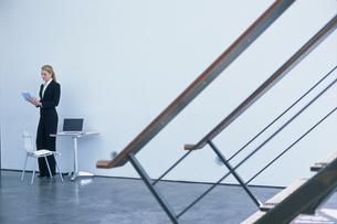 階段越しの壁際のスーツ姿の女性の写真素材 [FYI03365555]
