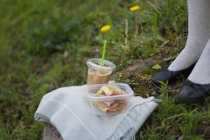 コーヒーとサンドイッチと女性の足元の写真素材 [FYI03365795]
