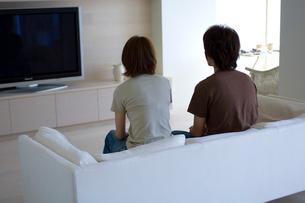 ソファーに座るカップルとテレビの写真素材 [FYI03365834]
