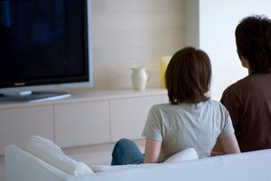 ソファーに座るカップルとテレビの写真素材 [FYI03365841]