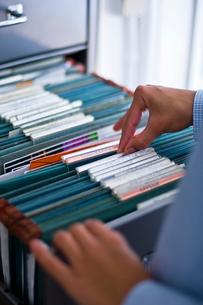 キャビネットの中のファイルを見る女性の手元の写真素材 [FYI03365872]