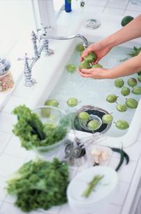 キッチンで果物を洗う手元の写真素材 [FYI03365931]