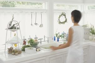 窓辺のキッチンと女性の後ろ姿の写真素材 [FYI03365948]