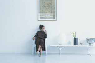 壁際に置いた白いイスに座っている女性の写真素材 [FYI03366055]