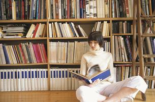 本棚の前の床に座った女性の写真素材 [FYI03366715]