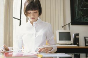 デスクで書類を見る女性の写真素材 [FYI03366772]