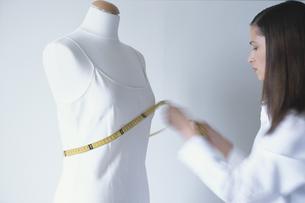 トルソーにメジャーをあて計る女性の写真素材 [FYI03366801]