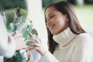 花束を貰う白いセーターを着た女性の写真素材 [FYI03366852]