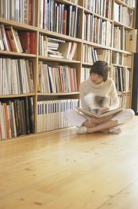 本棚の前に座り本をめくる女性の写真素材 [FYI03366929]