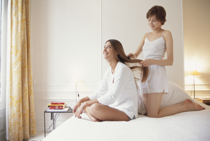 ベットルームの白いインナー姿の女性2人の写真素材 [FYI03366964]