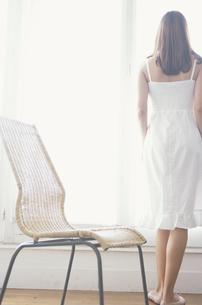 窓辺に立つ女性 手前に籐の椅子の写真素材 [FYI03367030]