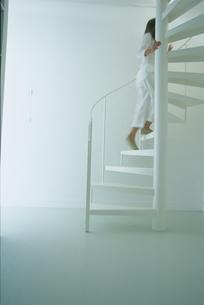 白い螺旋階段を上る女性の写真素材 [FYI03367309]