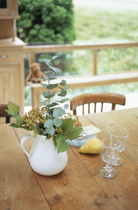 テーブルに置いたビンに生けた花の写真素材 [FYI03367529]