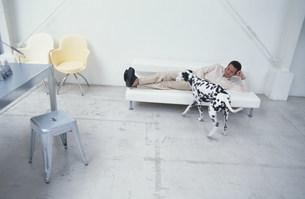 白いソファに寝転ぶ男性と犬(ダルメシアン)の写真素材 [FYI03368029]