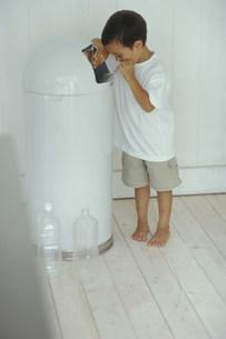 ゴミ箱を覗くハーフの男の子の写真素材 [FYI03368075]