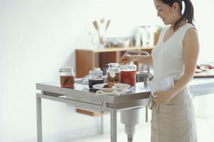 フルーツのコンポートに生クリームをのせる日本人女性の写真素材 [FYI03368085]