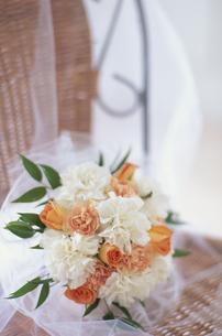 籐の椅子の上 白カーネーション・オレンジバラのブーケの写真素材 [FYI03368162]