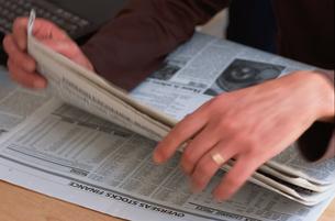 英字新聞を捲る男性の手の写真素材 [FYI03368285]