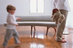 ソファの前を走る外国人子供と男性の写真素材 [FYI03368293]