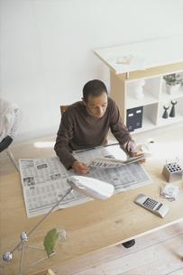 デスクで新聞を読む男性の写真素材 [FYI03368324]