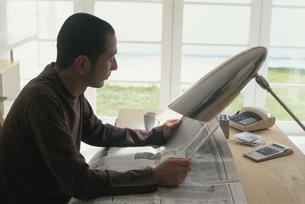 デスクで新聞を読む男性の写真素材 [FYI03368326]