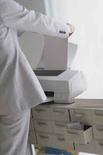プリンターに紙をセットする人の写真素材 [FYI03368345]